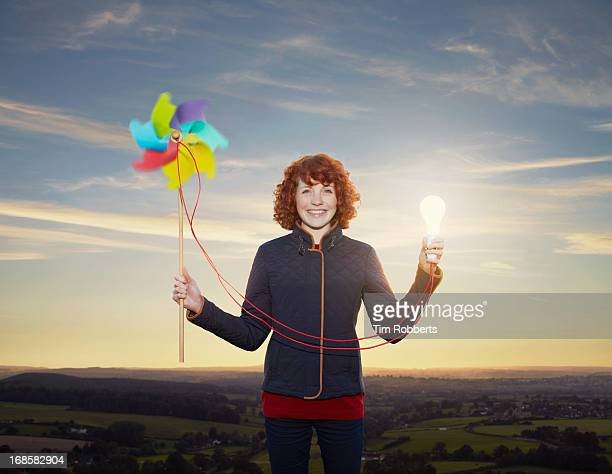 Young woman with wind turbine powered bulb at dusk