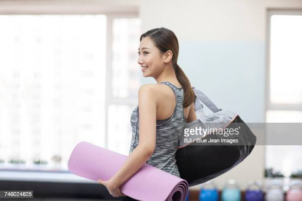 Young woman with yoga mat at gym
