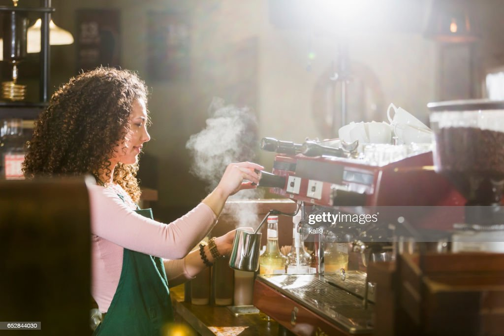 Young woman working as barista at coffee shop : Stock-Foto