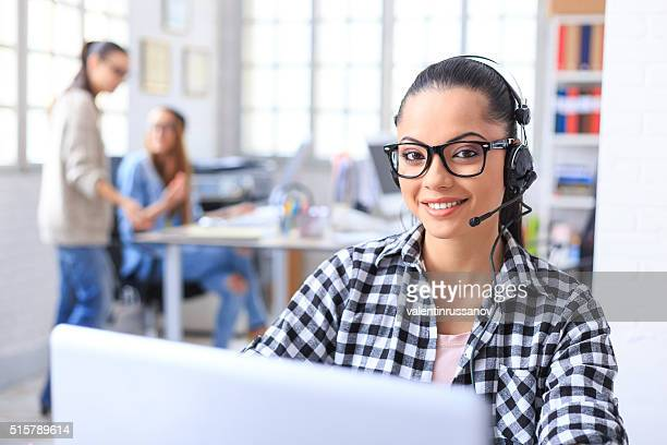 Young woman working as call center representative