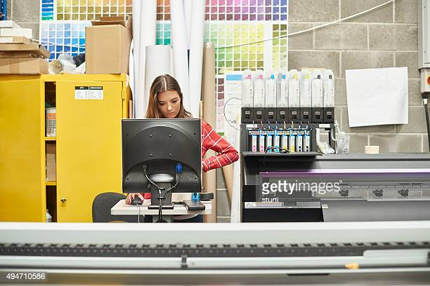 Junge Frau, die Arbeit an einem digitalen Print-Firma