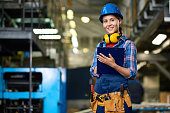 Portrait of female construction worker working in modern plant looking at camera, smiling filling in papers on clipboard