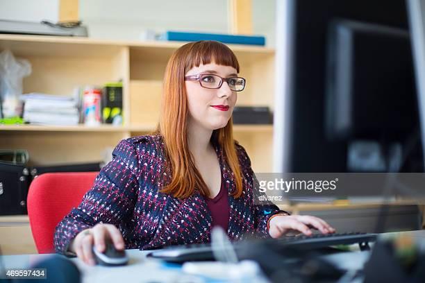 Junge Frau arbeitet auf ihrem Schreibtisch