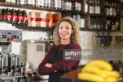 Young woman working behind counter at coffee shop : Stockfoto