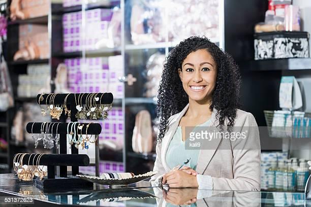 Mujer joven trabajando en tienda minorista Detrás del mostrador de