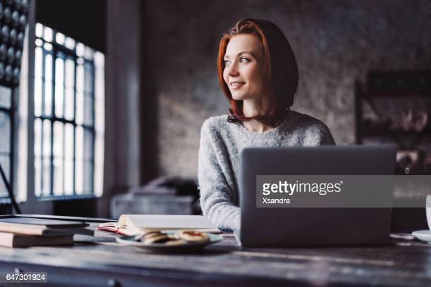 Junge Frau in ein Loft-Apartment mit einem Laptop arbeiten