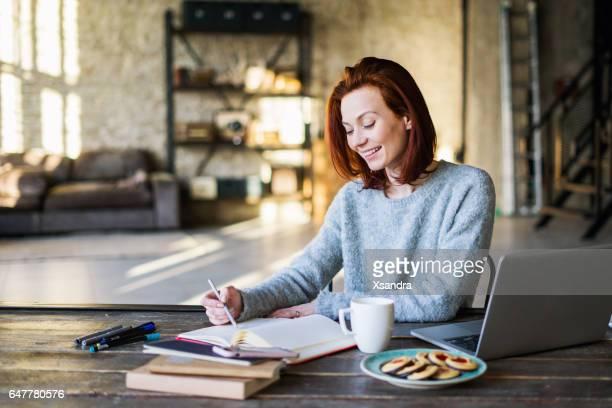 Jeune femme travaillant dans un appartement loft avec un ordinateur portable
