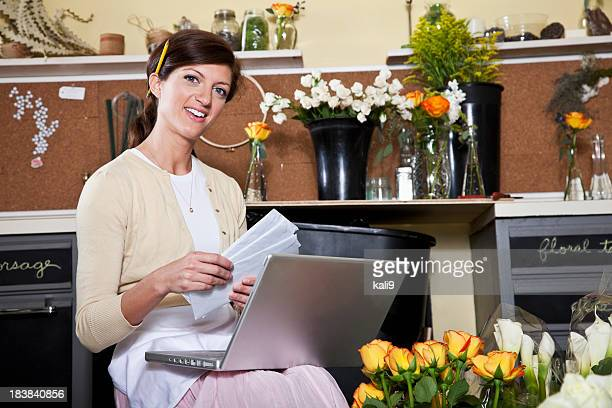 Young woman working in florist shop with laptop