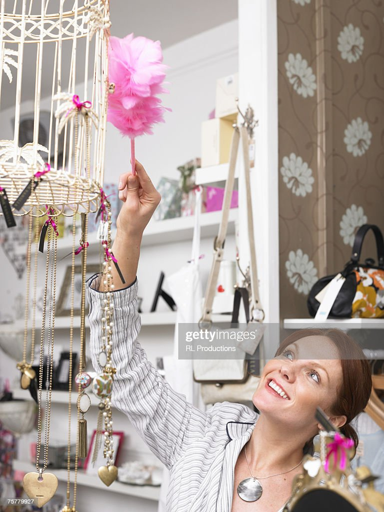 Young woman working in gift shop dusting bird cage : Stock Photo