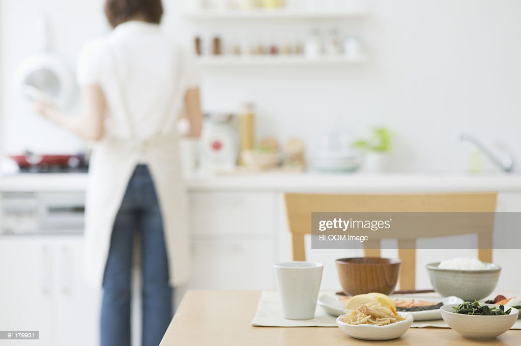 Young woman working in kitchen, rear view, focus on foreground : Stock Photo