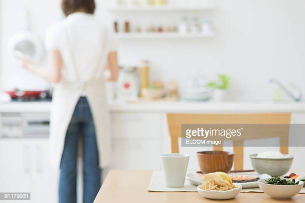 Young woman working in kitchen, rear view, focus on foreground