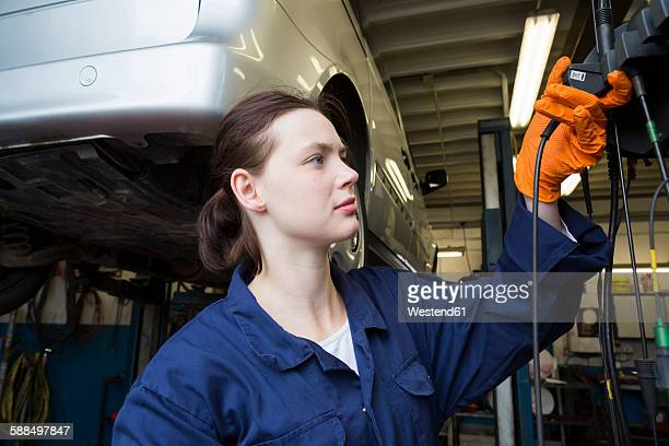 Young woman working in repair garage using electric screw driver