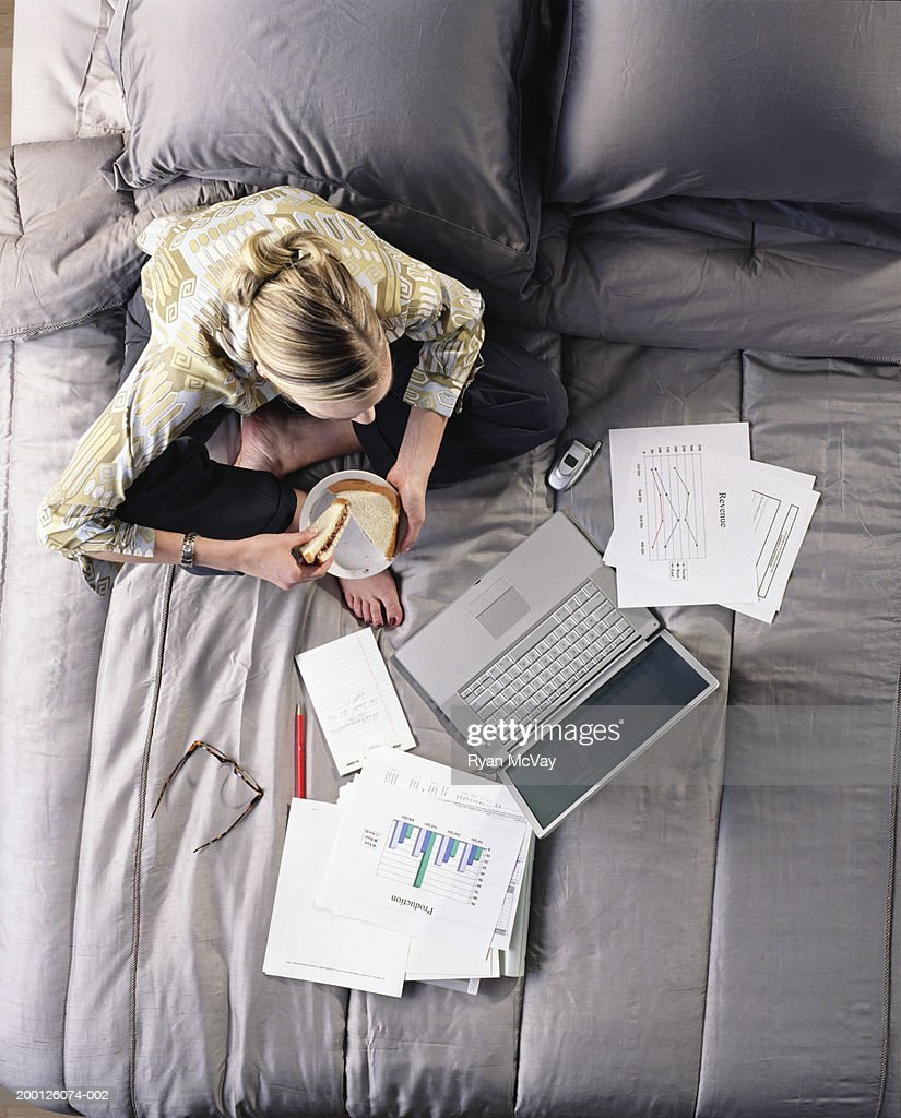 Young woman working on laptop in bed, overhead view : Stock Photo