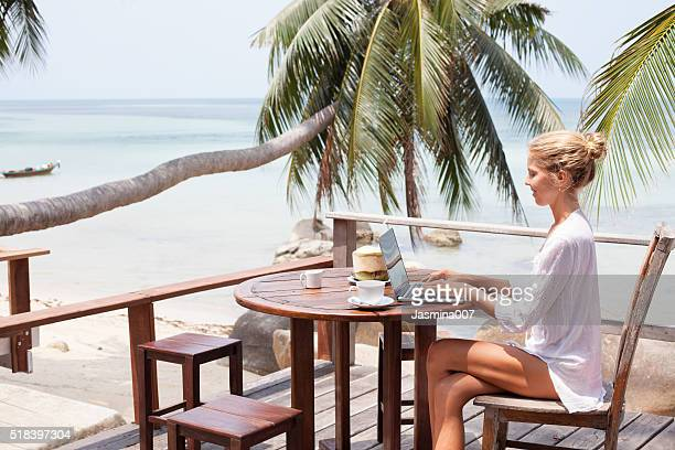 Junge Frau arbeiten mit Laptop mit Kaffee und von der jungen Kokosnuss