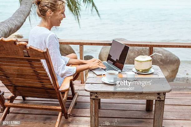 Young woman working on laptop with coffee and young coconut