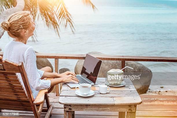 Jeune femme travaillant sur ordinateur portable avec du café et un jus de jeune noix de coco