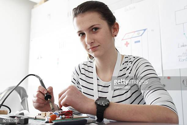 Young woman working on optical sensor in an electronic workshop