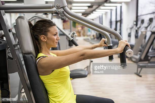Young woman working out on exercise machine in a gym.