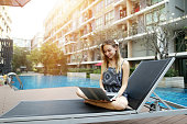 young female woman working with new laptop pc computer outdoors remotely as freelancer close to blue swimming pool and apartment building on sunny day with sunshine. Concept of working in tropical cou