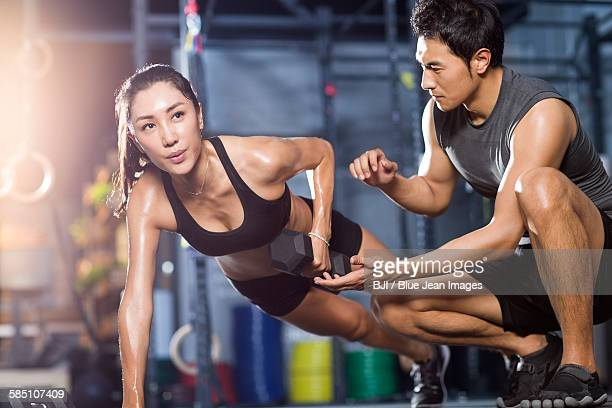 Young woman working with trainer in gym