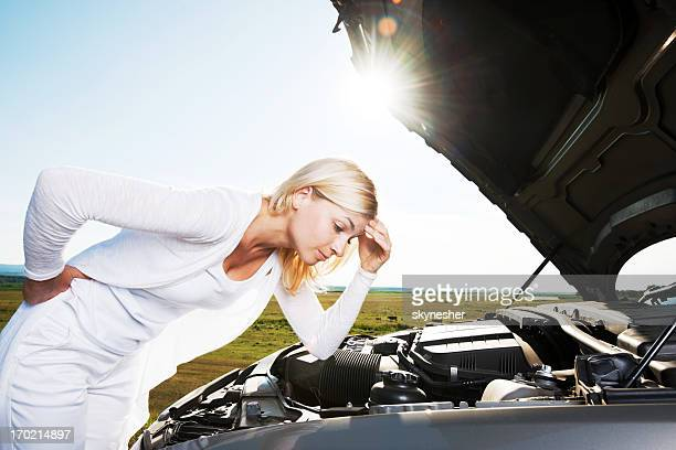 Young woman worried because her car broke down.