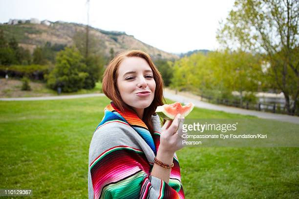 Young woman wrapped in a blanket eating watermelon