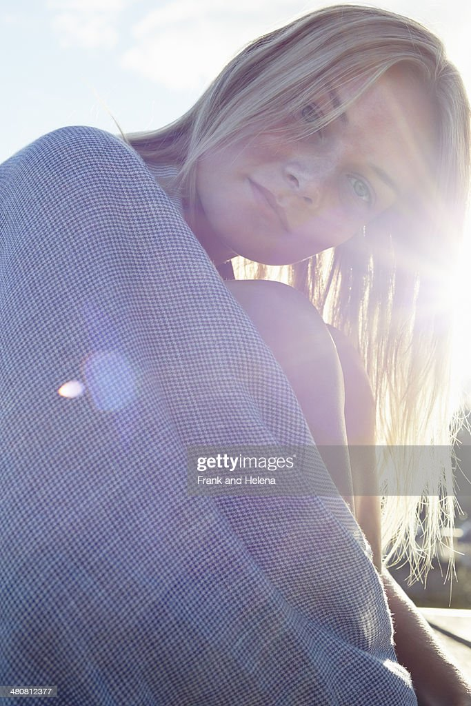 Young woman wrapped in a blanket in sunshine