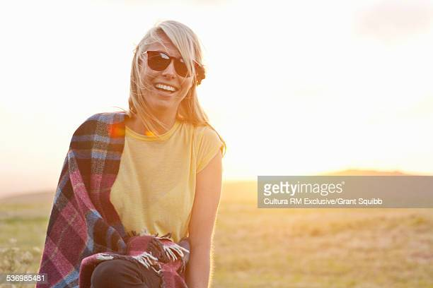 Young woman wrapped in blanket in rural field at sunset, Dorset, England