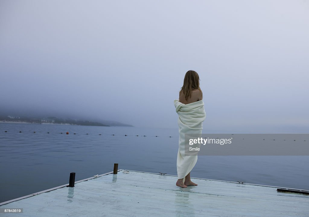 young woman wrapped in blanket looking out to sea : Stock Photo