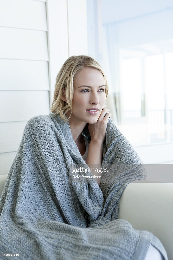 Young woman wrapped in blanket
