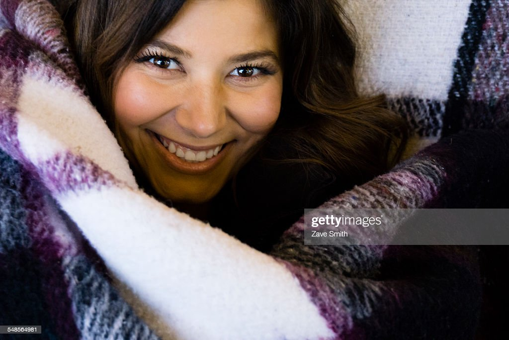 Young woman wrapped in blanket, portrait
