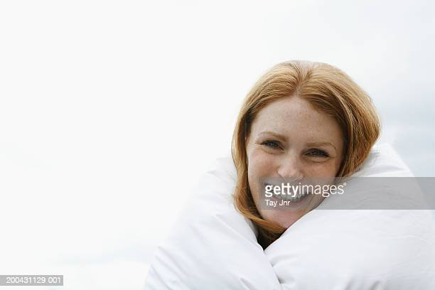 Young woman wrapped in duvet, smiling, portrait, close-up