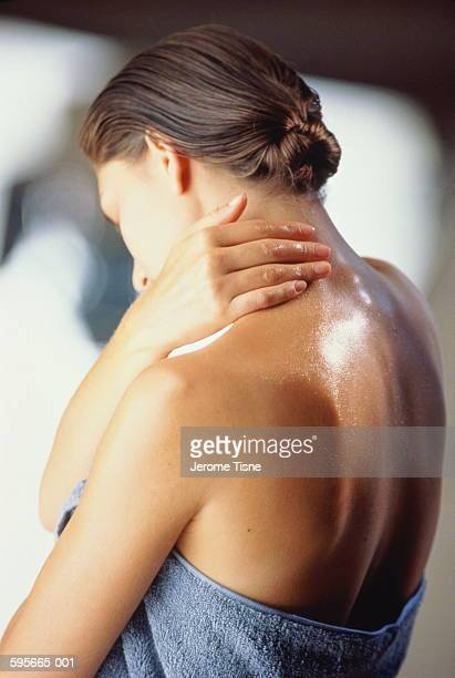 Young woman wrapped in towel rubbing cream on neck, rear view