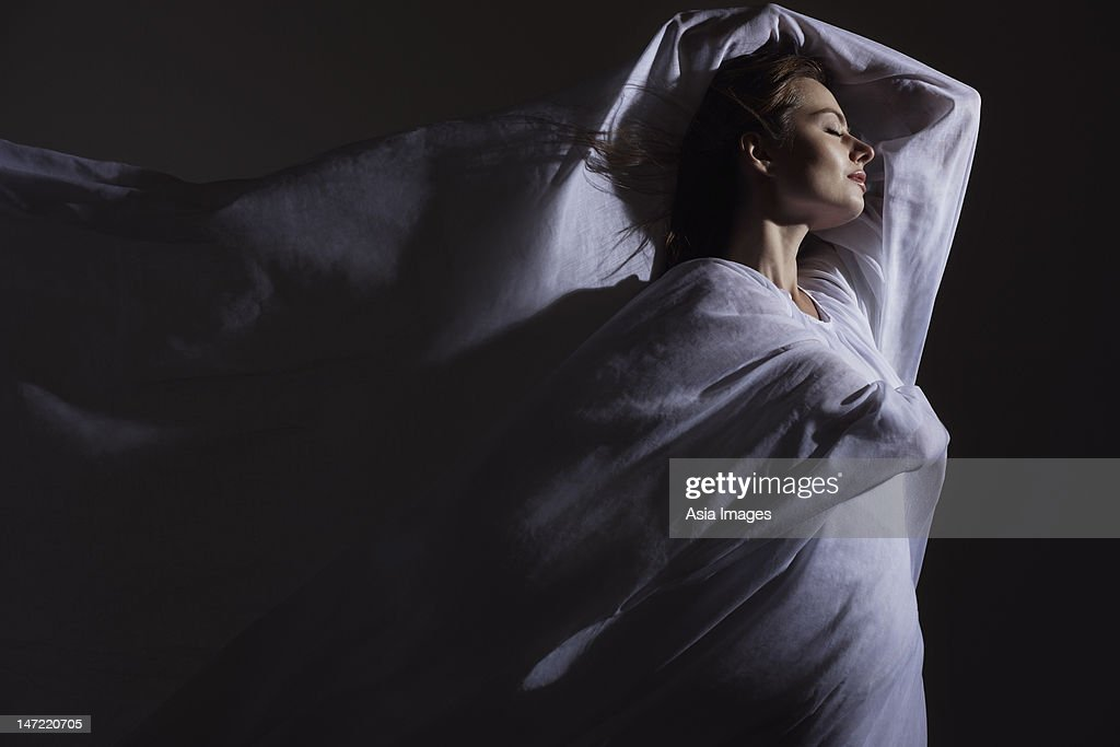 Young woman wrapped in white fabric : Stock Photo