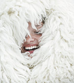 Young woman wrapped in wool blanket, eyes closed, laughing, close-up