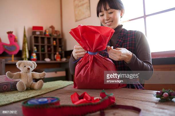 Young woman wrapping Christmas present