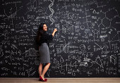 Young woman writes math equations on chalkboard