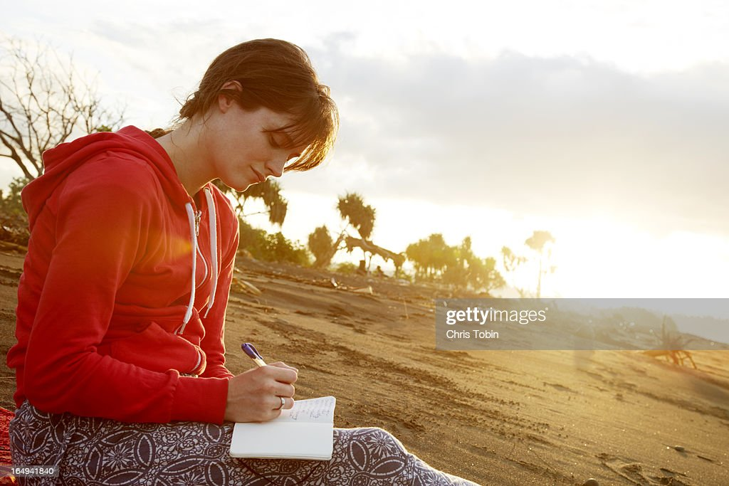 Young woman writing in journal on the beach : Stock Photo