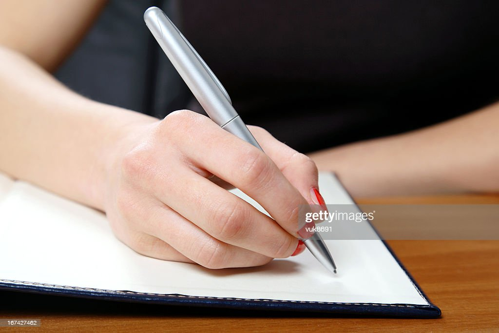 Young woman writing in office : Stock Photo