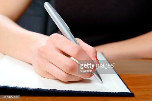 Joven mujer escribiendo en oficina : Foto de stock