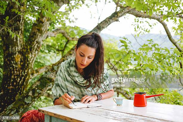 Young woman writing in the beautiful nature