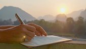 Young woman writing travel notes in diary during sunrise with beautiful sun light and mountain landscape on the background, close-up.