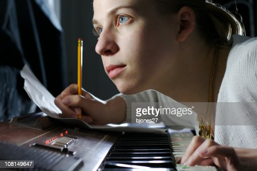 Young Woman Writing Music and Playing Piano : Stock Photo
