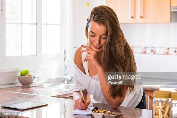 Young woman writing on notepad in kitchen