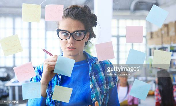 Young woman writing on post-it notes on glass wall