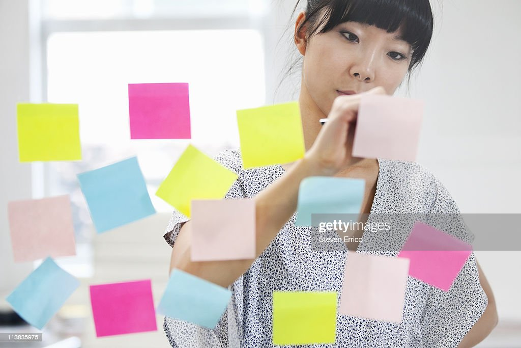 Young woman writing on sticky notes : Stock Photo