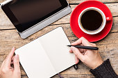 Young woman writing or drawing into notepad using tablet PC and enjoying cup of coffee. Top view freelancer workplace image