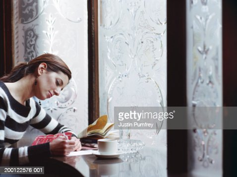 Young woman writing postcard in pub