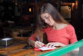 young woman writing postcards at a café