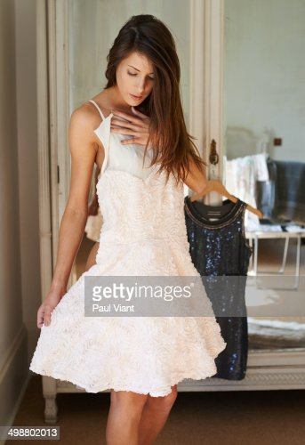 Young womanrying on dresses in bedroom